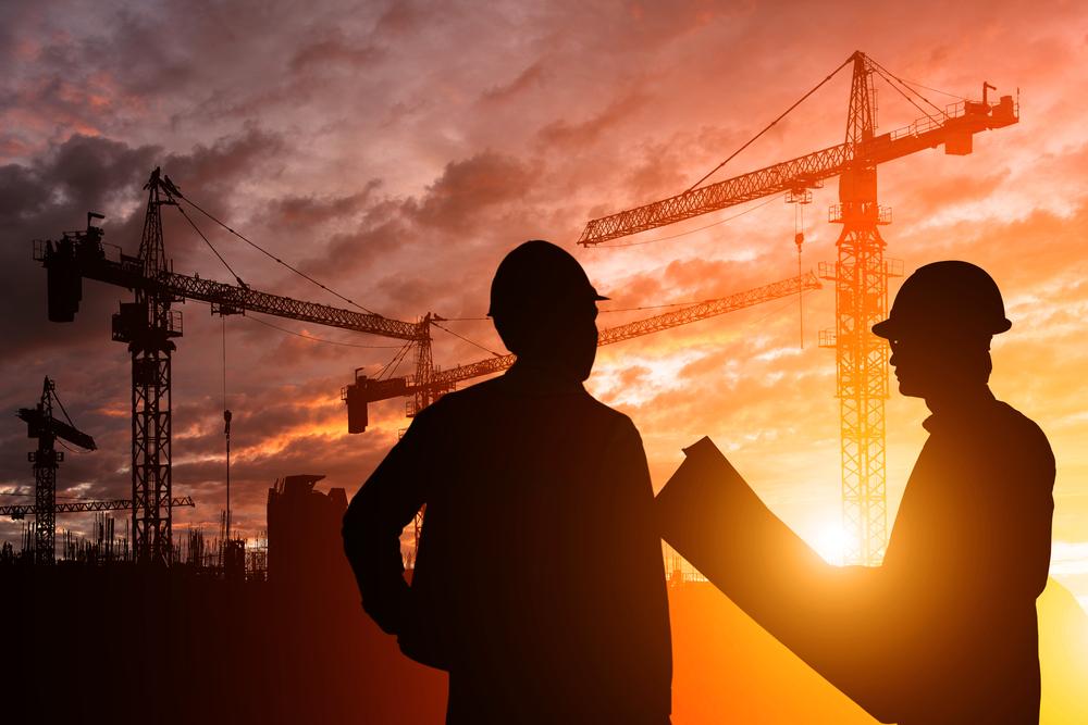 dois engenheiros analisando um projeto em um ambiente de construção.