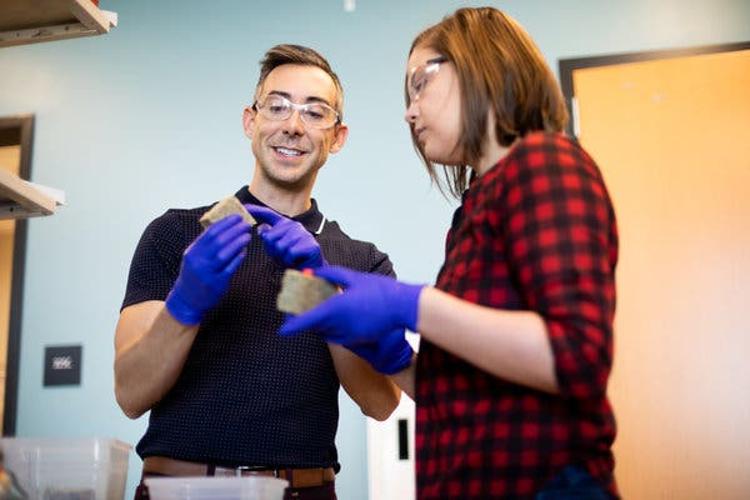 À esquerda, Wil Srubar - engenheiro estrutural da Universidade do Colorado, em Boulder. À direita, a aluna de doutorado em ciência e engenharia de materiais, Sarah Williams. Ambos segurando tijolos de matéria de construção feitos de cianobactérias