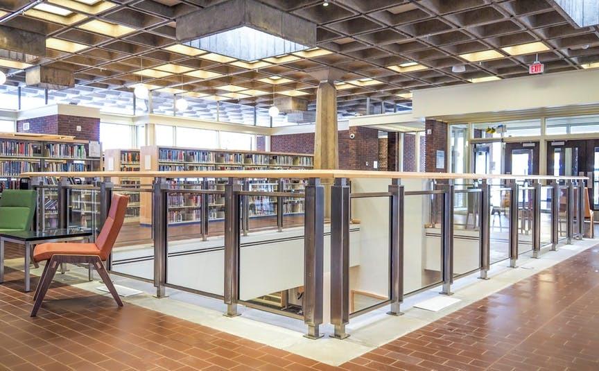 Interior do andar principal da Biblioteca Arvonne Fraser, com estantes e cadeiras. No teto, há lajes nervuradas.