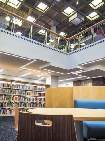 Interior do andar inferior biblioteca Arvonne Fraser, com estantes, cadeiras e sofá. No teto são usadas lajes nervuradas.
